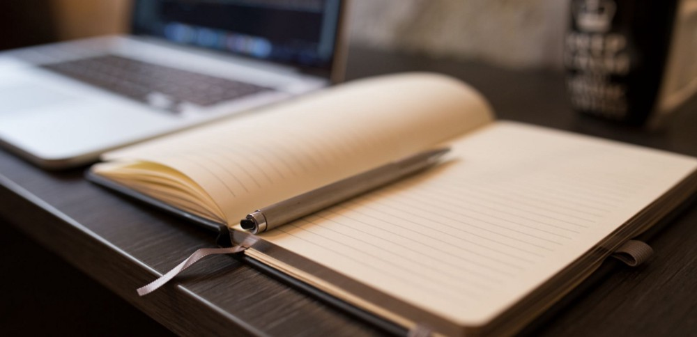 An empty notebook laying open next to a laptop. The laptop is in the background.